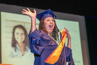 Asma Isack waves to the crowd during the College of Nursing's August commencement at Centennial Hall.
