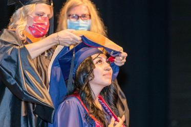 Ariel Alonzo is hooded during the College of Nursing's August commencement at Centennial Hall.