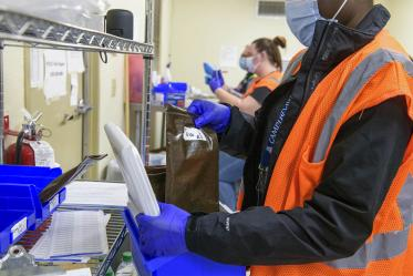 UArizona Campus Health Pharmacy Technician Pearl Craig (right) gathers vaccines that are ready to be distributed to people at the scheduled walk-in location at the Ina E. Gittings Building.