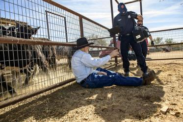 Rio Rico emergency medical technicians set up field equipment to assist rancher Leon Keller with his injury. (Note: This was a simulated accident scene for demonstration purposes.)