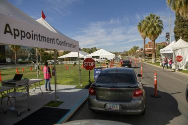 A volunteer confirms appointments as people arrive at the COVID 19 drive-through vaccine distribution site on the University of Arizona mall.