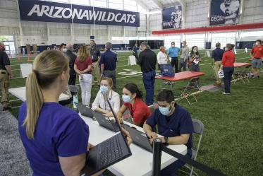A new use for a practice field, testing is conducted in this climate controlled temporary clinic set up inside the Cole and Jeannie Davis Sports Center on the University of Arizona main campus.