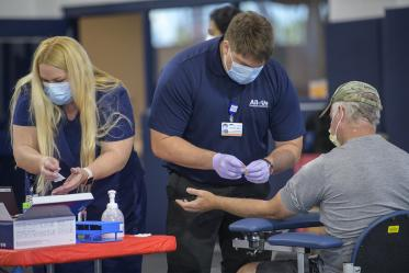 Health care workers assist with blood sample collection. More than 4,500 people are scheduled to have their blood drawn in the first few days of testing.