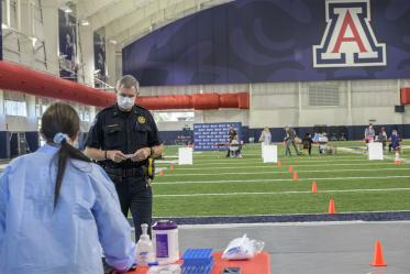 A Tucson-area police officer waits to be called to give a blood sample for the antibody test.