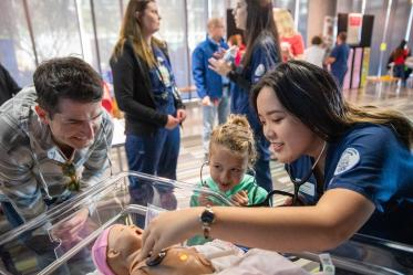 Volunteers from the University of Arizona College of Nursing check infant manikin for a heartbeat inside the Wildcat Play Hospital.