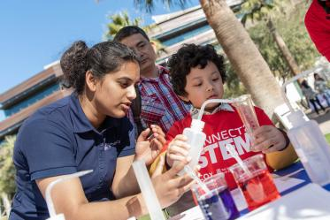 Volunteer with the University of Arizona College of Pharmacy demonstrates chemistry with a young visitor.