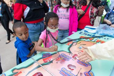 Children practice medical skills on life-sized Operation game sponsored by Phoenix Children's Hospital.