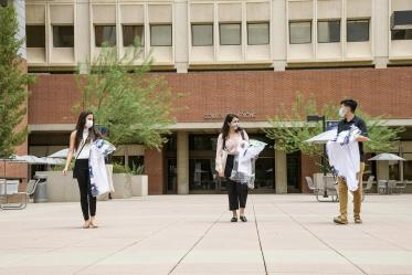 White coats in hand, three new members of the Class of 2024 leave the College of Medicine – Tucson building. From left: Lupita Molina, Julia Alvarenga Couto and Lawrence Sun.