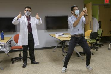 First-year medical student Daniel Nguyen of Santa Rita House tries on his white coat while first-year medical student Ahmed Al-Shamari takes a selfie with his new colleague.