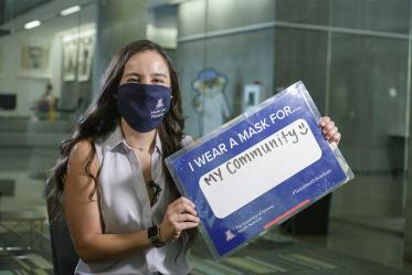 """First-year College of Medicine – Phoenix student Natalie Alteri shares a sign that reads, """"I wear a mask for my community."""" Alteri is one of 32 students from the Colleges of Medicine in Tucson and Phoenix to be awarded a Primary Care Physician Scholarship this fall."""