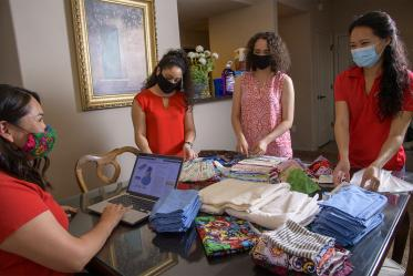 College of Medicine – Tucson student Thomasina Blackwater looks up mask-making instructions while fellow students Nicole Bejany, Guadalupe Davila and Lynn Pham prepare donated supplies for Navajo seamstresses to use to create personal protective equipment.