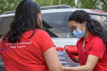 College of Medicine – Tucson fourth-year student Thomasina Blackwater and Lynn Pham of the college's Association of Native American Medical Students and the Rural Health Professions Program load hand sanitizer into vehicles for delivery to the Navajo Nation.