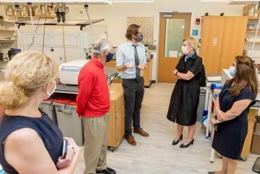 Deborah Birx, MD, coordinator of the White House Coronavirus Task Force, listens as Ryan Sprissler, PhD, staff scientist and manager of the UArizona Genetics Core, explains the antibody testing process. UArizona President Robert C. Robbins, MD, and others, joined Dr. Birx during her visit.
