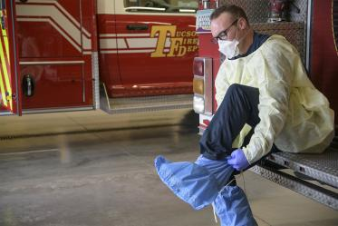 Tucson Fire Department's Taylor Parrish puts on a protective gown and boot coverings to prevent spread of disease before entering the home a possible COVID-19 patient.