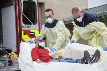 Firefighters Taylor Parrish and Chris LaFave wrap Jonathan Sexton, PhD, in a protective barrier to demonstrate how to prevent further spread of a virus during an ambulance trip to the hospital.