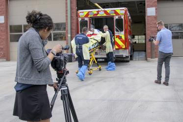 University of Arizona Health Sciences' Viola Watson and Erich Healy document the loading of a patient into ambulance. Healy works for the Mel and Enid Zuckerman College of Public Health and the Western Regional Public Health Training Center.
