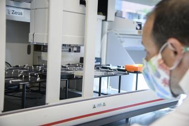 Matthew Kaplan, manager for University of Arizona Functional Genomics Core, evaluates the Biomek robot prior to performing antibody testing.