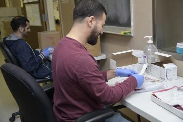 Biorepository laboratory techs Ayman Sam (left) and Brandon Jernigan (right) complete the final step to assemble the COVID-19 sample collection kit.
