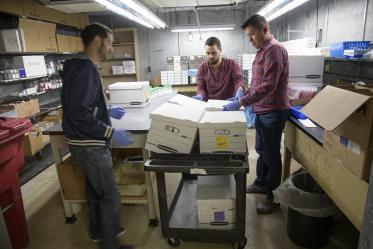 Biorepository laboratory technicians Brandon Jernigan, Ayman Sami, and Jose Camarena, load boxes of COVID-19 sample collection kits to deliver to Banner-University Medical Center Tucson.