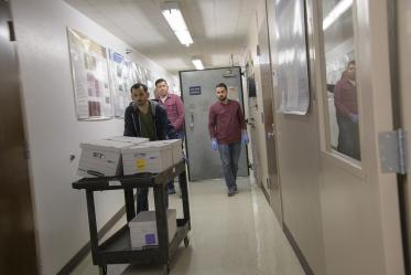 Biorepository lab technicians use a cart to move boxes of sample collection kits to deliver to Banner-University Medical Center Tucson.