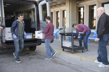 Lab Techs stand by before loading the kits into a Banner van as local media prepares to film.