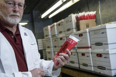Standing inside a freezer, David Harris, PhD, shows a COVID-19 specimen collection kit inside a biohazard bag. Dr. Harris is executive director of University of Arizona Health Sciences Biorepository, and spearheaded the effort to create local testing kits so more health care providers in Arizona could administer the test to find out if patients had the virus that causes COVID-19. The effort began in March, and produced thousands of test collection kits per week.