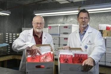 David T. Harris, PhD, (left) and Michael Badowski, PhD, (right) stand in a freezer with sample collection kits ready for delivery to Arizona health care providers.