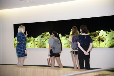 """Students touring the Health Sciences Innovation Building view """"Gold Waves,"""" a video art installation on the second floor."""