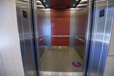 Decals placed on elevator floors mark six feet, helping visualize appropriate distance.
