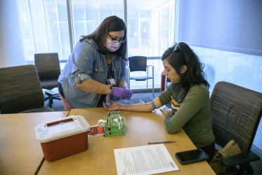 University of Arizona researcher Yvonne Castaneda draws blood from a test subject who has had COVID-19. This helps researchers to verify the accuracy of the antibody test, a key step conducted in April on the path to creating highly accurate tests.