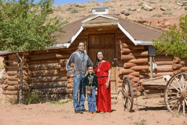 Vanessa Jensen, MD, a University of Arizona College of Medicine – Tucson surgery alumna, with her husband and son in front of their family Hogan in Tuba City, Ariz. on the Navajo Nation.