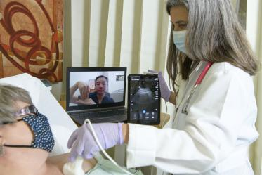 Dr. Elaine Situ-LaCasse (pictured on the laptop) receives a livestream of the exam results and assists in diagnosing a standardized patient during a telehealth training consultation with Julia Brown, MD, emergency department medical director at the Copper Queen Community Hospital in Bisbee, Arizona.