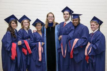 Kacey Ernst, PhD, MPH, poses with students at the 2014 convocation.