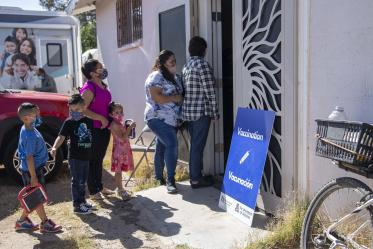 People gather outside a community center for a MOVE-UP clinic hosted by UArizona Health Sciences in the rural town of Aguila, Arizona, to get COVID-19 vaccine shots.