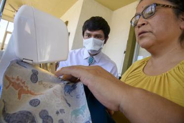 University of Arizona College of Medicine – Tucson student Aaron Bia watches as Navajo seamstress Theresa Hatathlie-Delmar sews a surgical cap with material donated in the college's PPE drive.