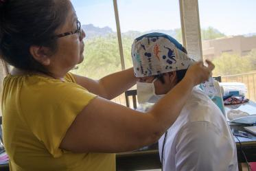 Navajo seamstress Theresa Hatathlie-Delmar checks the fit of a surgical cap on College of Medicine – Tucson student Aaron Bia.