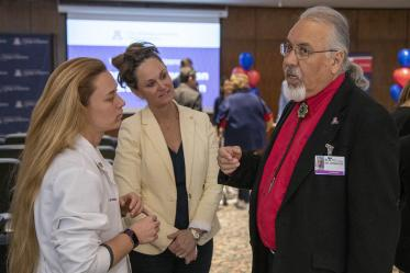 Dr. Carlos Gonzales speaks with Primary Care Physician scholarship recipient Hannah Shy, left, and her mother, center.