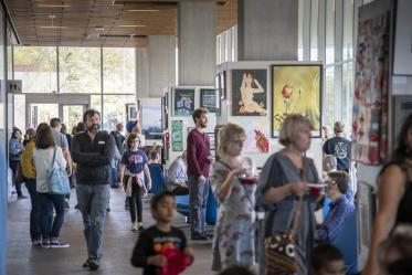 """Attendees mingle in the Bioscience Research Laboratories lobby during the 10th annual """"On Our Own Time"""" art exhibit, featuring art made by University of Arizona employees and their immediate family members."""