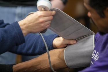 Street Medicine Phoenix co-founder Justin Zeien checks a patient's blood pressure.