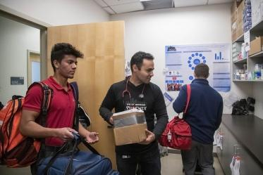 Student volunteer Eashan Das, left, co-founder Jeffery Hanna, center, and co-founder Justin Zeien, right, put away supplies in the Street Medicine Phoenix storage area on College of Medicine – Phoenix campus after the Grace Lutheran Church street run.