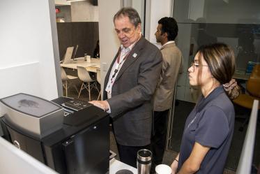 University of Arizona Senior Vice President of Health Sciences Michael D. Dake, MD, uses the new espresso machine inside the Faculty Commons + Advisory
