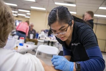 Merryl Lopido, simulation operations specialist for ASTEC, places fake skin on a woman to simulate a wound sustained during a flight. In this scenario, a drone landed on an airplane's wing and exploded, injuring several passengers and forcing the plane to land.