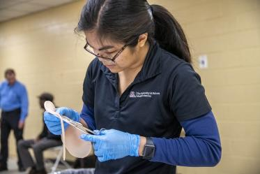 Merryl Lopido, simulation operations specialist for ASTEC, cuts synthetic skin to be placed on a volunteer to simulate a realistic-looking wound.