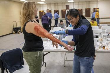 With outstretched arms, volunteer Pamela Leonard prepares to roleplay an airplane passenger injured by a midair explosion. Merryl Lopido, simulation operations specialist for ASTEC, uses special-effects makeup to create fake burns.