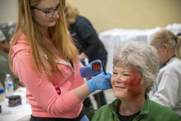 Sadie Keesler, an undergraduate at the University of Arizona College of Science and ASTEC volunteer, creates a burn effect on volunteer Deborah Tilley. Tilley said she was excited to Skype her grandchildren and show them her simulated wounds.