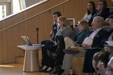 Melissa Colchado, chief of staff of management and policy at the University of Arizona Health Sciences, reads questions sent via text to Senior Vice President for Health Sciences Michael D. Dake, MD.