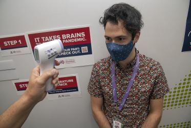 Graduate student Gregory Branigan receives a temperature check outside of the Center for Innovation in Brain Science at Bioscience Research Laboratories. The center implemented COVID-19 screening with daily online health surveys and temperature scans for all faculty, staff and students entering buildings.