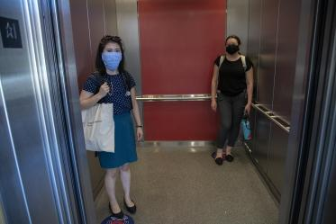First-year College of Medicine – Tucson students Aileen Lee (left), and Brianne Davis (right) stand on signs placed on elevator floors marking six feet.
