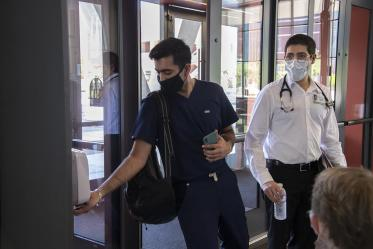 First year College of Medicine – Tucson student Yasi Suri, left, uses hand sanitizer before he and fellow first year student Jonathan Yasmeh head to a class in the Health Science Innovation Building.