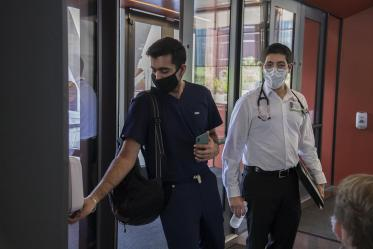 First year College of Medicine – Tucson student Yasi Suri, left, puts sanitizer on his hands before he and fellow first year student Jonathan Yasmeh  head to a class in the Health Science Innovation Building.